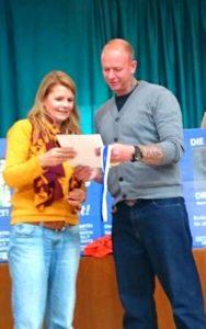 Claudia Krüger, Stadträtin in Düsseldorf und Beisitzerin im Bundesvorstand überreicht Patrick Dau die MUT-Medaille