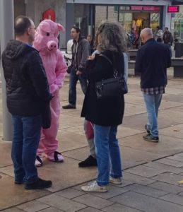 Svea im Schweine-Kostüm spricht mit Passanten